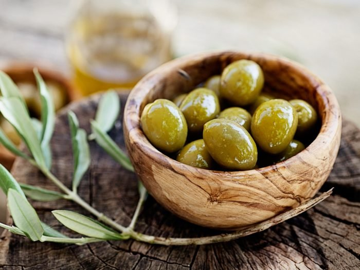 A wooden bowl of fresh olives on a wooden plank