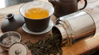A cup of oolong tea with a teapot and oolong tea leaves on a wooden table
