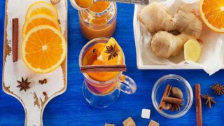 A flat lay picture of oranges, spices, sugar, and tea - all the necessary ingredients required to make a cup of orange tea