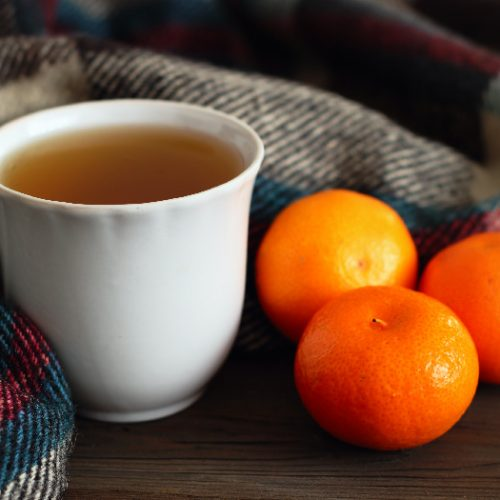 A cup of tea with a woolen scarf and oranges next to it.