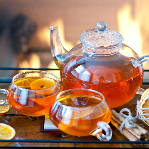A glass tea set with orange-flavored tea, with a fire in the fireplace in the background