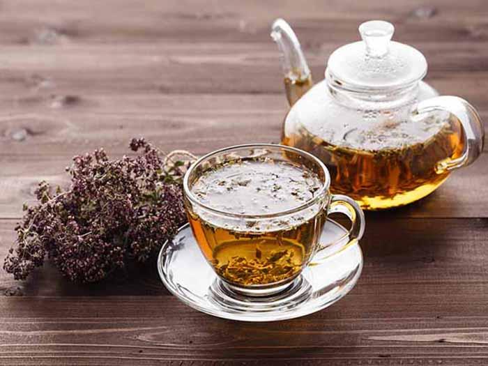 Oregano tea kept in a teapot next to a cup of oregano tea, on a wooden platform