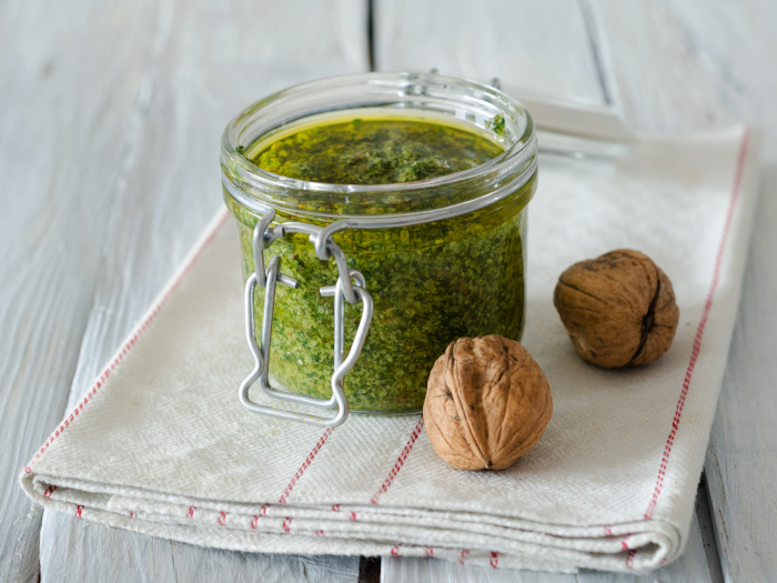 Walnut parsley pesto in a jar on a white background
