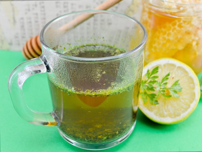 A cup of tea with halved lemon on a green table