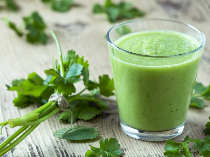 A glass of green juice along with parsley leaves in the background
