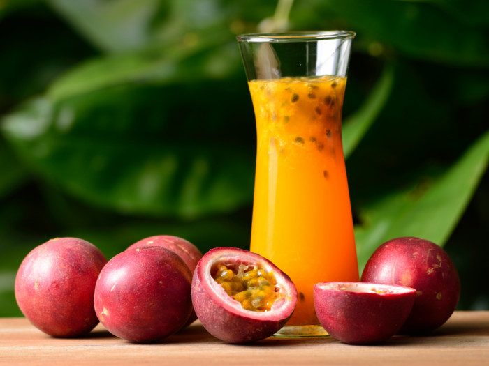 A glass of fresh passion fruit juice kept next to ripe passion fruits atop a table