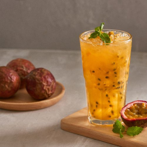 A glass of passion fruit juice kept next to passion fruits atop a table