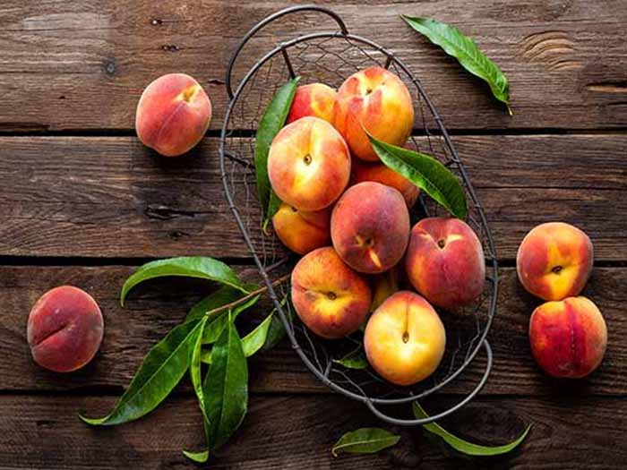 peaches on a wooden counter with peach leaves