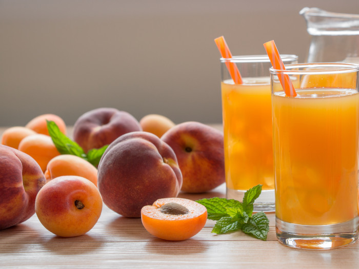 Two glasses with yellow-colored liquid and a straw, placed on a wooden surface. A jug at the back. Peaches at the base