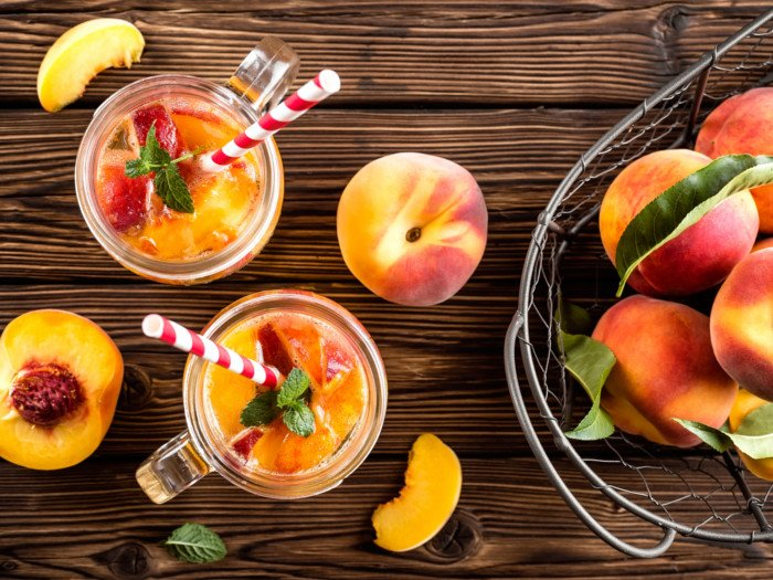 Two jars filled with cold peach tea or peach beverage surrounded by peach fruits