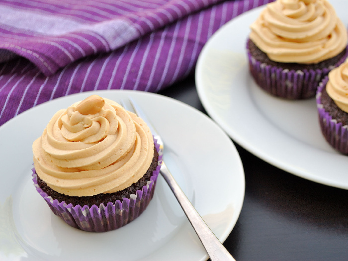 Peanut butter frosting on chocolate cupcakes on a white plate on a table with a purple napkin