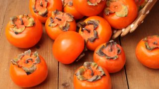 Close up of fresh and tasty orange persimmons on a wooden table