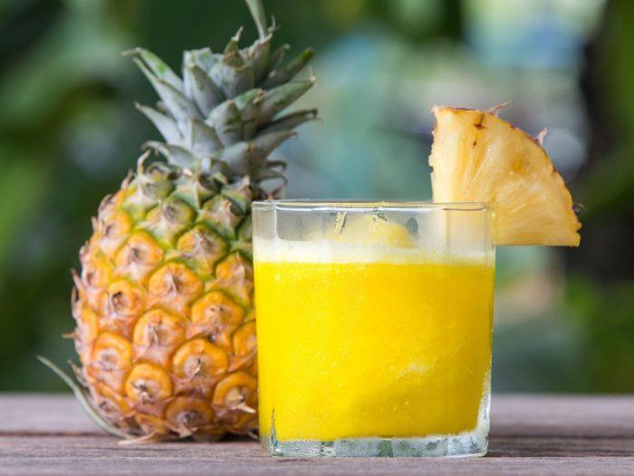 A large glass of pineapple juice with lemon garnish