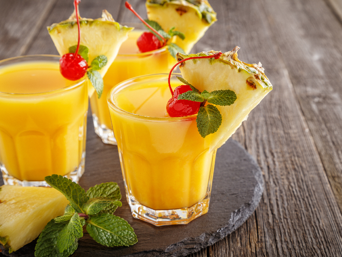 Glasses of pineapple juice with pieces of pineapple, cocktail cherry and mint on wooden table