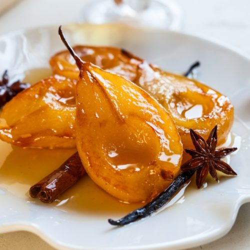 Poached pears with spices in syrup on a white plate