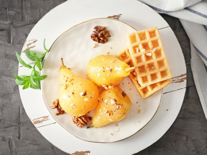 Delicious poached pears in wine and waffles on a plate