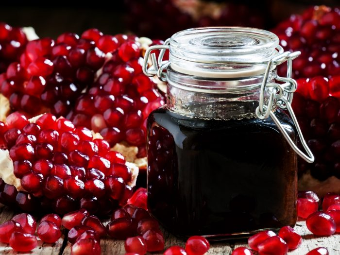 A jar filled with pomegranate molasses on a bed of pomegranate seeds