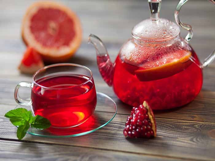 Pomegranate tea in a cup and teapot with citrus slices on a wooden counter