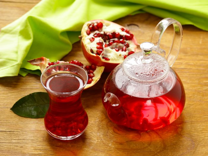 A small kettle and tea cup filled with pomegranate tea and two halves of pomegranates around