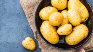 A pan filled with boiled potatoes on a grey background