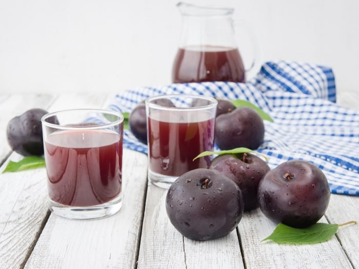 Two small glasses of prune juice surrounded by a couple of prunes and a huge jug full of prune juice