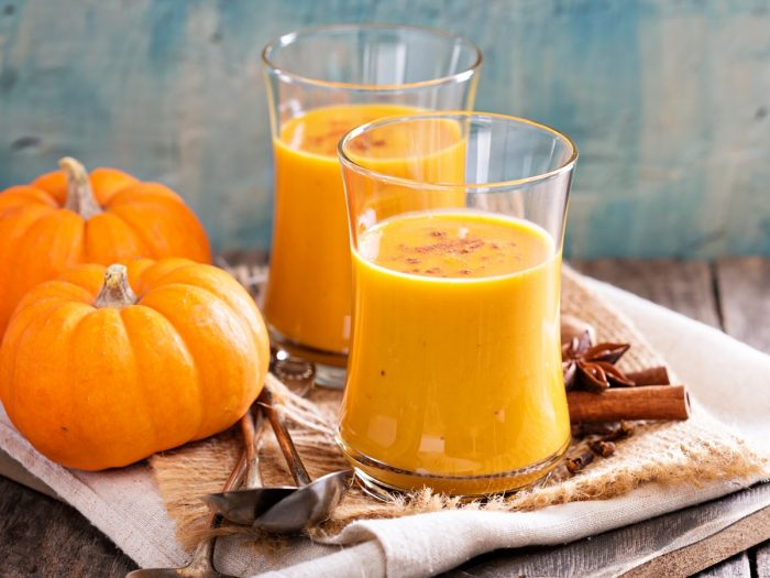 Two glass jars filled with pumpkin juice kept atop a table next to pumpkins