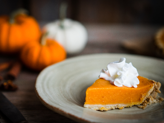 White and orange pumpkins and spices in the background of a slice of pumpkin pie topped with whipped cream