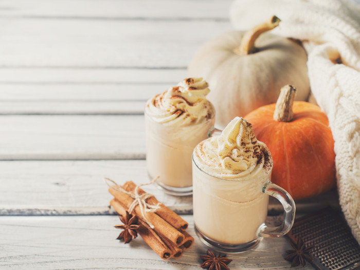 Two cups of pumpkin spice latte with cinnamon and star anise and pumpkins kept beside them atop a white table