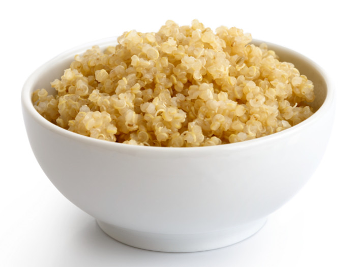 A bowl of cooked quinoa in a white bowl with white background