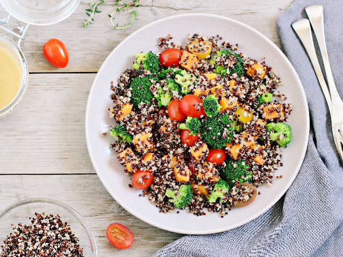 Quinoa salad with broccoli, sweet potatoes and tomatoes on a rustic wooden table. Three-color quinoa salad