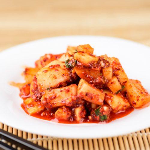 A close up shot of radish kimchi kept on a white plate with chopsticks