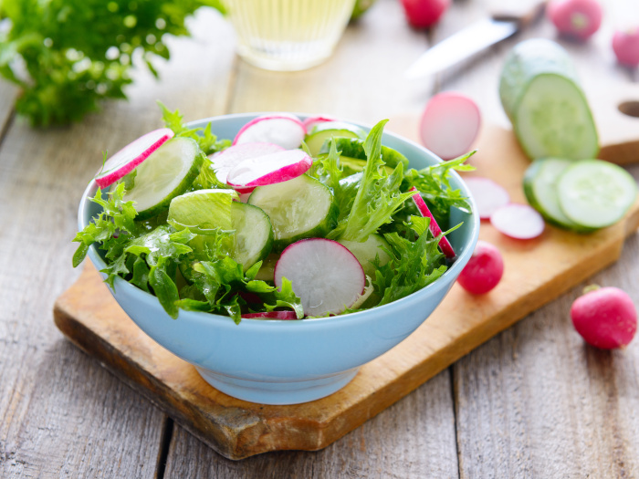 A white bowl with radish and cucumber salad on a wooden cutting board with sliced vegetables behind
