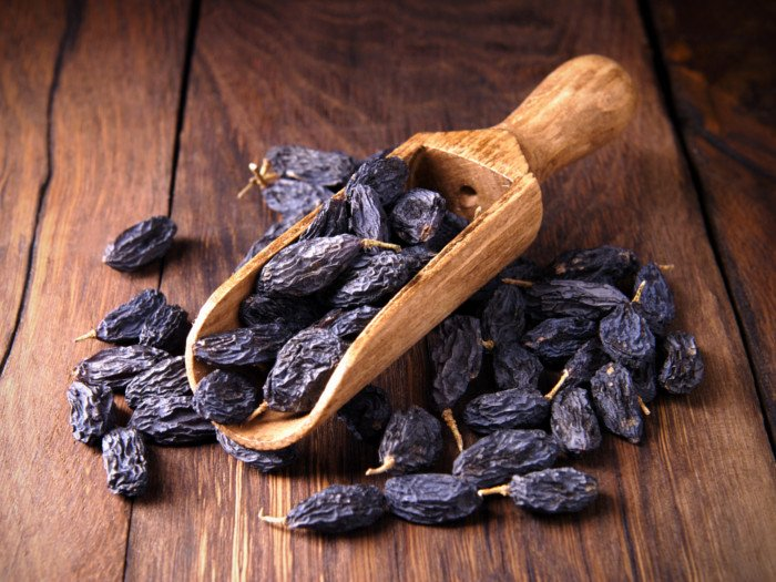 a wooden spoon full of black raisins kept on a table