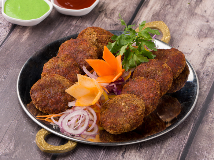 Mutton kebab pieces on a plate decorated with salad and served with sauces