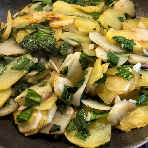 Fried potatoes and ramps on a black plate