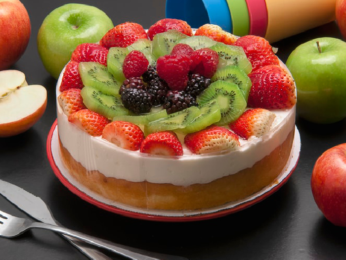 Paleo Vanilla cheesecake garnished with fresh fruits like strawberries, kiwis, and blue berries, kept atop a plate on a table