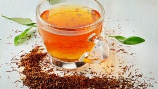 A cup of rooibos tea and loose leaves on a white table