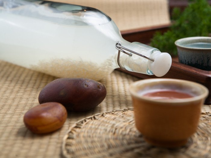A bottle of rice wine and two pebbles on a table