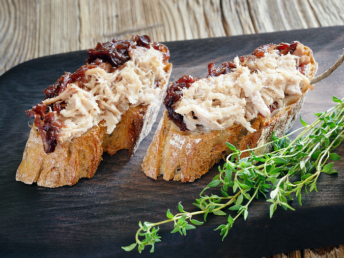 Meat rillettes on bread and a glass jar with the jam covering rillettes
