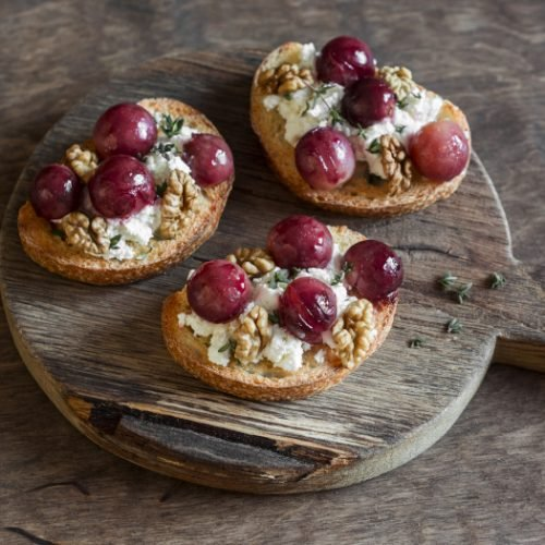 Roasted grape and goat cheese bruschetta on a wooden background.