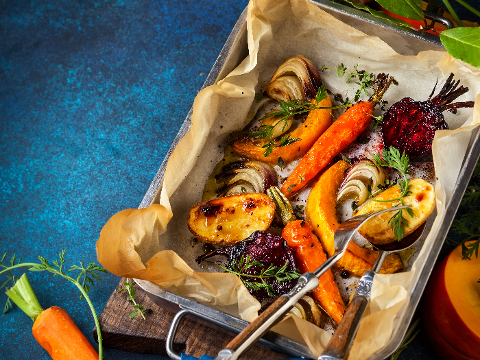 Oven roasted vegetables with garlic and herbs on the baking tray.