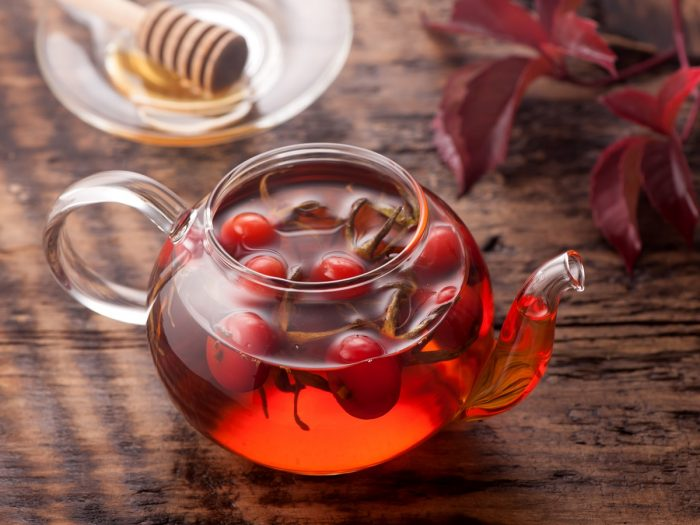 A kettle containing rose hip tea and rosehips and a wooden dipper on a saucer and red leaves on a wooden table