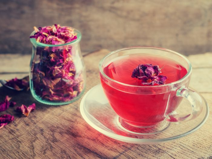 A jar filled with dried rose leaves and a cup of rose tea on a wooden table