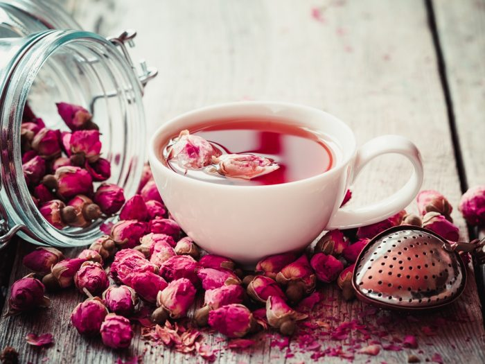 A cup of rose tea with rose buds around