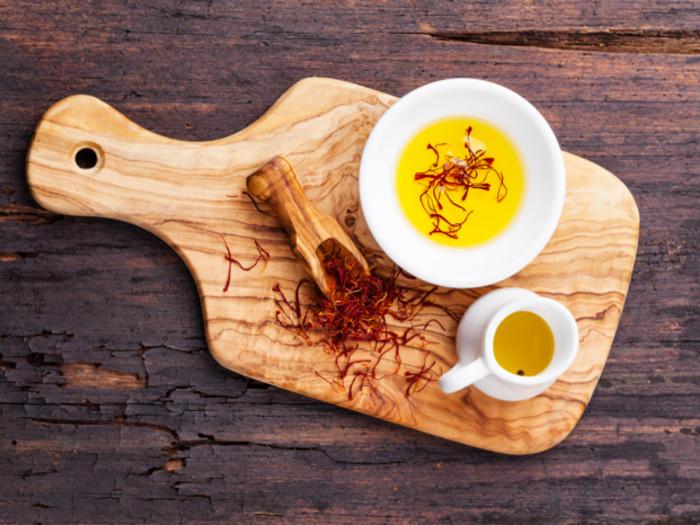 Saffron herb in a spoon, next to saffron oil and saffron tea on a wooden board