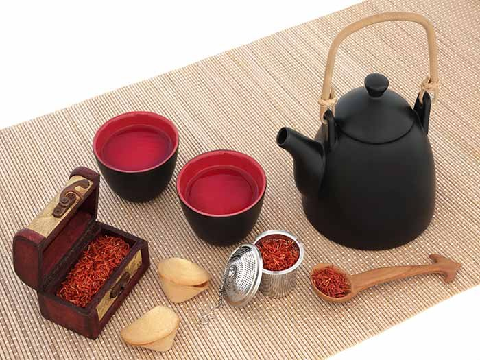 Saffron tea, saffron spice in tins, and a black teapot on a table