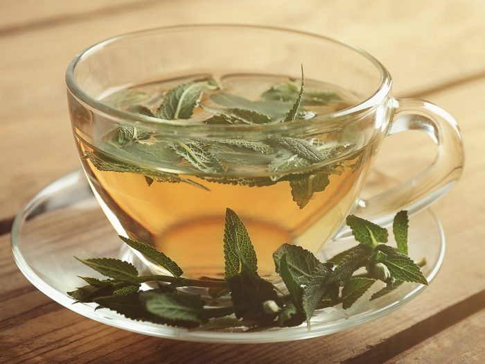 A cup of tea infused with sage leaves
