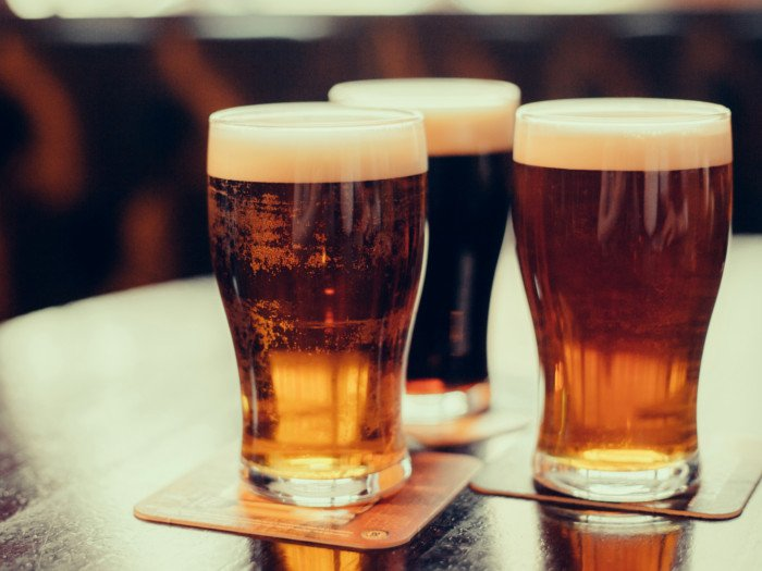 Three beer glasses with foam on top