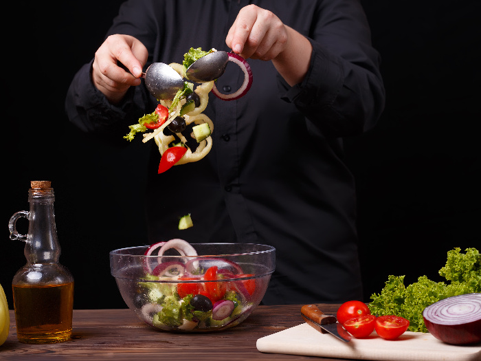 Chef neatly mixing fresh summer salad in a bowl