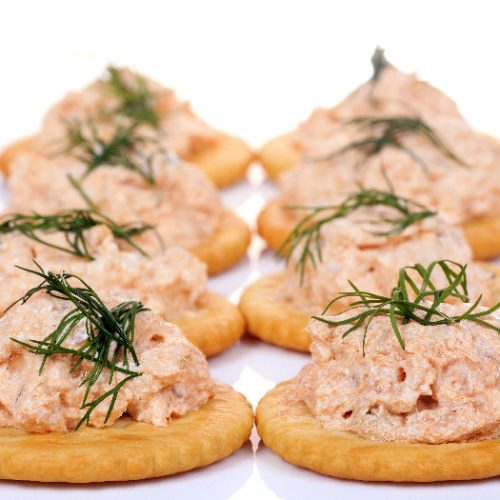 Salmon spread on cracker cookies on white background